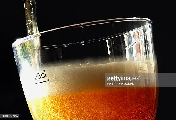 A picture taken on October 1 2012 shows beer poured into a glass of beer in Lille northern France The level of taxation of beer will increase in...