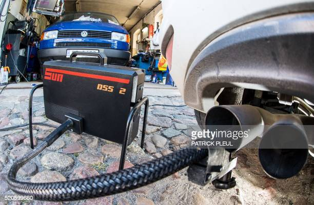 Picture taken on October 1 2015 in a car workshop in Frankfurt an der Oder eastern Germany shows a measuring tube sticking in the exhaust pipe of a...