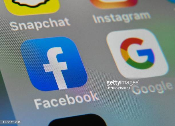 A picture taken on October 1 2019 in Lille shows the logos of mobile apps Facebook and Google displayed on a tablet