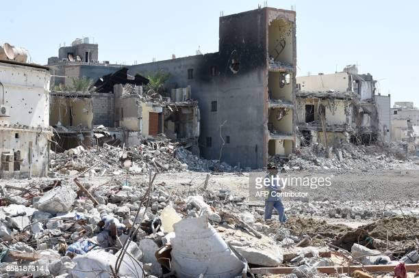 A picture taken on October 1 during a tour guided by Saudi authorities shows a man walking past destruction in the Shiitemajority town of Awamiya in...