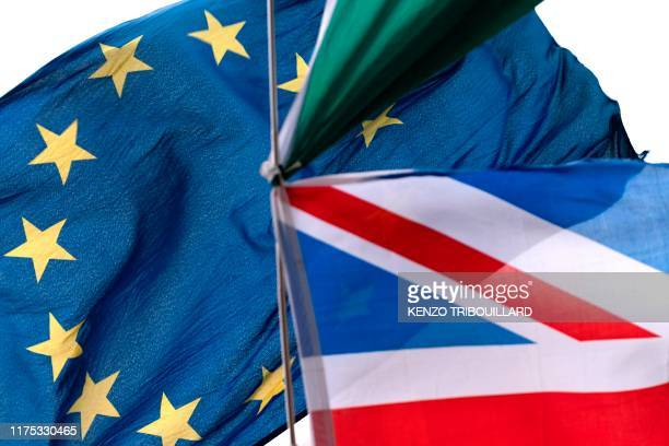 A picture taken on October 11 2019 shows the flag of the United Kingdom and the European Union waves outside at the EU headquarters in Brussels on...