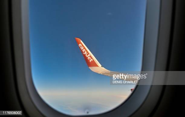 A picture taken on October 13 2019 shows a partial view of the wing of an EasyJet aircraft flying over the northern region