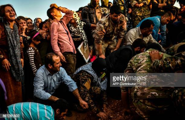 A picture taken on October 14 2017 in the Kurdish town of Kobane in northern Syria shows people mourning during the funeral of a Kurdish fighter who...