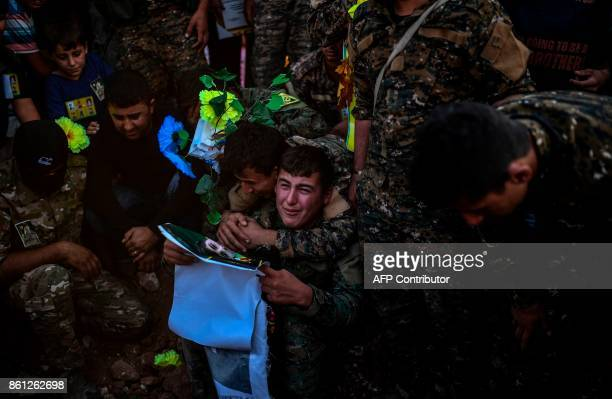 A picture taken on October 14 2017 in the Kurdish town of Kobane in northern Syria shows members of the Kurdish People's Protection Units mourning...