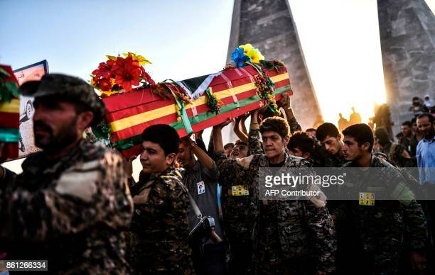 Picture taken on October 14, 2017 in the Kurdish town of Kobane in northern Syria shows members of the Kurdish People's Protection Units mourning as...