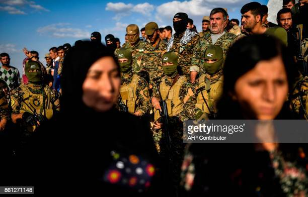 A picture taken on October 14 2017 in the Kurdish town of Kobane in northern Syria shows women and members of the Kurdish People's Protection Units...