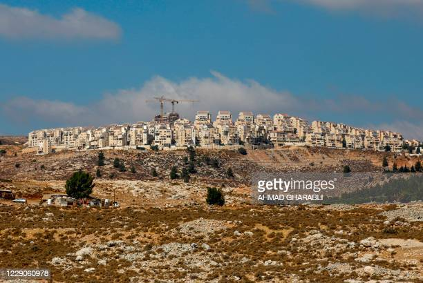 Picture taken on October 14, 2020 shows Israeli construction cranes and excavators at a building site of new housing units in the Jewish settlement...