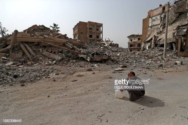TOPSHOT A picture taken on October 15 shows an Abd alIbrahim whose home was destroyed during fighting as he rests on his trip to supply water to his...
