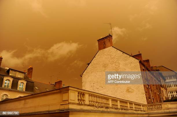 A picture taken on October 16 in central Rennes western France shows rooftops and the sky after it turned a yellowochre colour due to sand from the...
