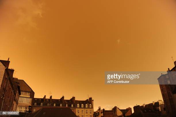 TOPSHOT A picture taken on October 16 in central Rennes western France shows rooftops and the sky after it turned a yellowochre colour due to sand...