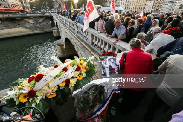A picture taken on October 17 2018 shows wreaths of flowers laid on the SaintMichel Bridge in Paris during a rally to commemorate a demonstration by...