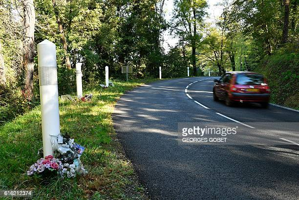 A picture taken on October 18 2016 shows a vehicle driving past flowers placed on the roadside in tribute to the the 43 victims of the road accident...