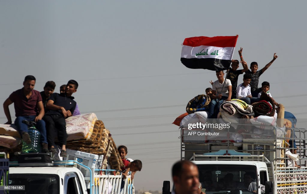A picture taken on October 18, 2017 shows displaced Iraqis, who fled from Hawija in 2014 to Kirkuk, riding in vehicles as they return to Hawija, after the town was retaken by Iraqi forces. /