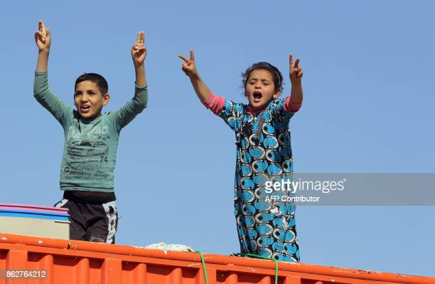 TOPSHOT A picture taken on October 18 2017 shows displaced Iraqis who fled from Hawija in 2014 to Kirkuk riding in vehicles as they return to Hawija...