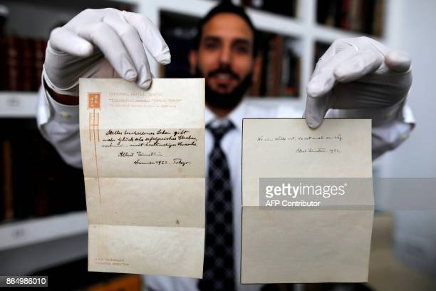 A picture taken on October 19 shows Gal Wiener owner and manager of the Winner's auction house in Jerusalem displays two notes written by Albert...