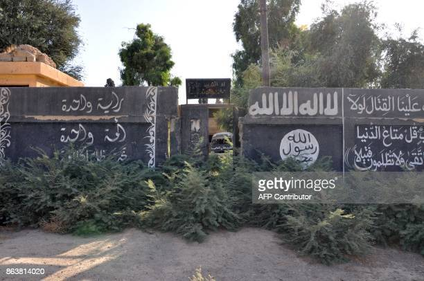 A picture taken on October 20 shows Islamic State group writting on a wall in the recently seized strategic Syrian town of Mayadeen / AFP PHOTO /...