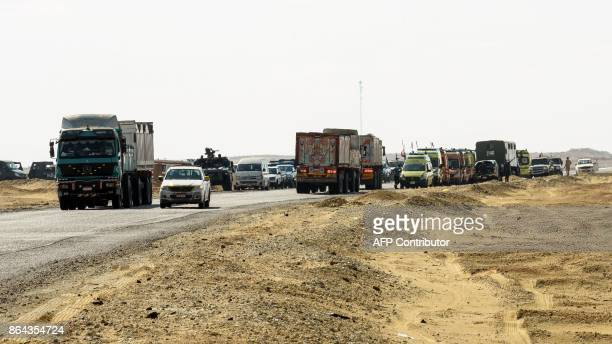 A picture taken on October 21 2017 shows Egyptian security forces' vehicles and armoured personnel carriers parked on the desert road towards the...