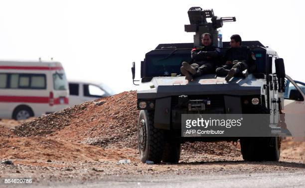 A picture taken on October 21 2017 shows members of the Egyptian security forces resting on the top of an armoured vehicle parked on the desert road...