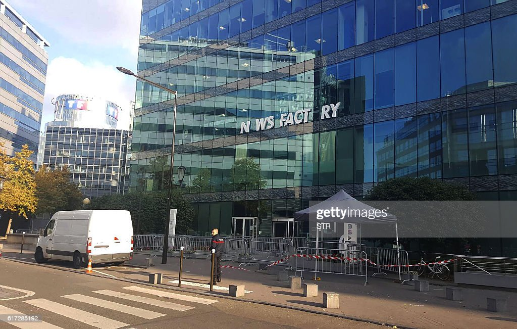 A picture taken on October 22, 2016 shows the facade of the French news channel iTele's headquarters with a sign reading 'News factory' after one of the letters fell, in Boulogne-Billancourt on October 22, 2016. Journalists of iTELE, on strike since October 17, reported that some of the offices of the news channel had been moved to make way for the arrival of the editorial board of Direct Matin, a news channel also owned by Vincent Bollore. Part of the editorial board of iTELE also discovered the installation a new brand on the facade of the building, 'news factory', a name that Bollore intends to give to his info center, which however was quickly withdrawn after several letters from the sign fell accidently, witnesses said. / AFP / STR