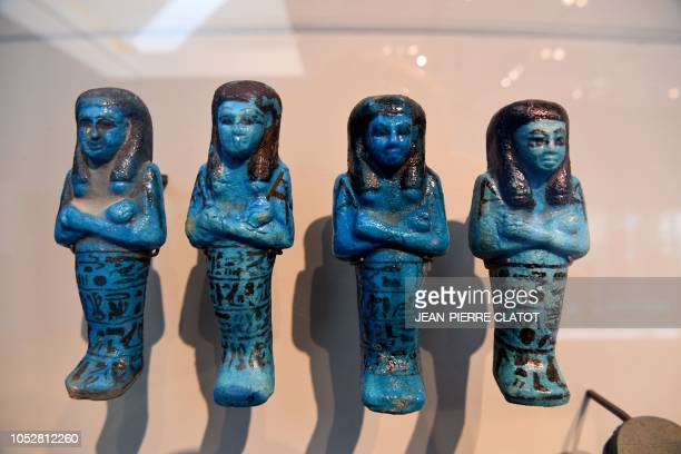 A picture taken on October 23 2018 in Grenoble southeastern France shows an Egyptian funerary statues part of the exhibition 'Serve the Gods of...
