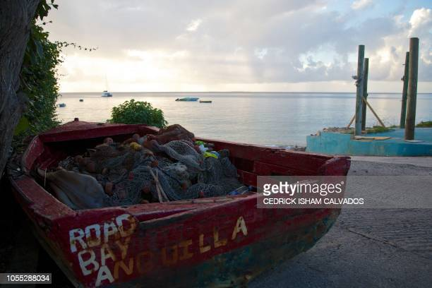 A picture taken on October 23 2018 shows a small fishing boat sits on the seashore in Anguilla a British overseas territory The tiny Caribbean island...