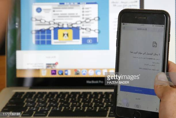 A picture taken on October 23 shows a Palestinian man holding a cell phone displaying the message this website is not accessible at an office in the...