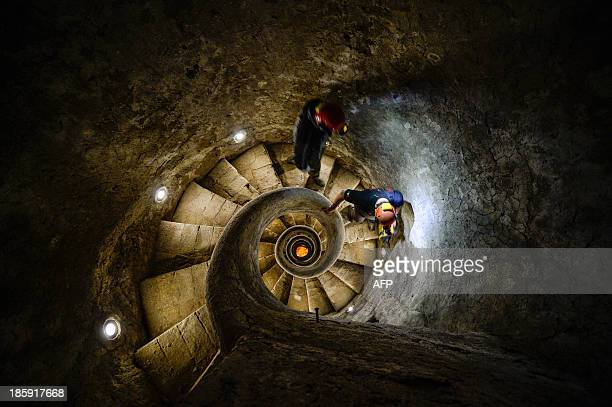 THUBURN A picture taken on October 25 2013 shows technicians in the stairs of 'The Snail' the Acqua Vergine aqueduct one of the 11 roman aqueducts...