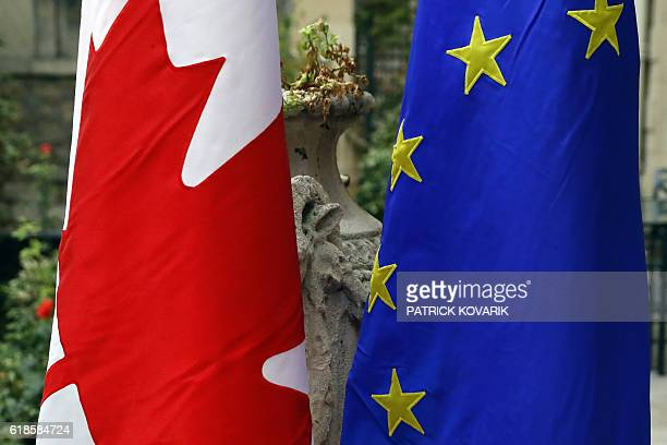 A picture taken on October 27 2016 shows Canada's national flag and European Union's flag in Paris / AFP / PATRICK KOVARIK