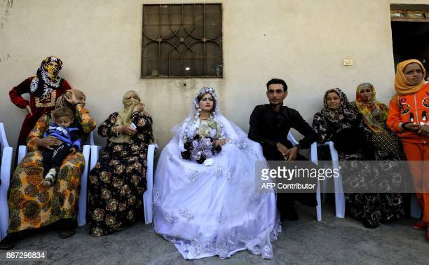 TOPSHOT A picture taken on October 27 2017 shows the groom Ahmed and bride Heba seated during the first wedding after the ouster of the Islamic State...