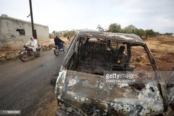 A picture taken on October 28 2019 shows Syrian bikers riding past a damaged car at the site of a suspected USled operation against Islamic State...