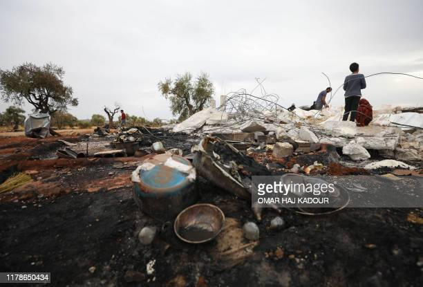 A picture taken on October 28 2019 shows Syrians sifting through the rubble at the site of a suspected USled operation against Islamic State chief...