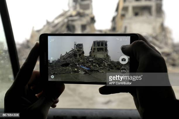 TOPSHOT A picture taken on October 28 shows a fighter of the Syrian Democratic Forces taking a picture with his phone from inside a car in the Syrian...