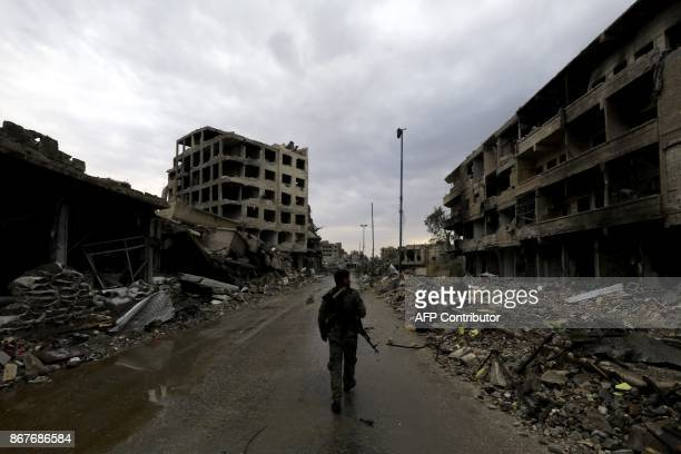 TOPSHOT A picture taken on October 28 shows a fighter of the Syrian Democratic Forces walking through an empty rubblefilled street surrounded by...