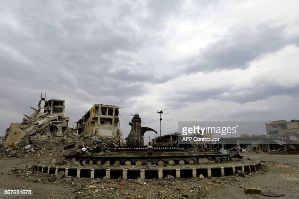 Picture taken on October 28 shows a view of a roundabout and damaged buildings in the Syrian city of Raqa. The US-backed SDF took full control of...