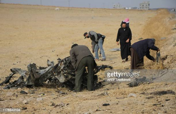 A picture taken on October 28 shows locals checking the wreckage at the spot where Abu Hassan alMuhajir the Islamic State group's spokesman was...