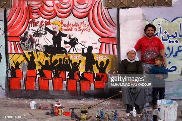 TOPSHOT A picture taken on October 28 shows Syrian artist Aziz alAsmar posing with relatives near a mural he painted in the town of Binnish in the...