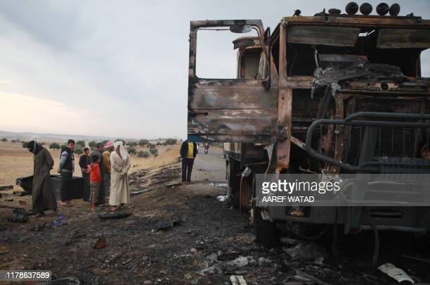 A picture taken on October 28 shows Syrian locals checking a destroyed truck at the spot where Abu Hassan alMuhajir the Islamic State group's...