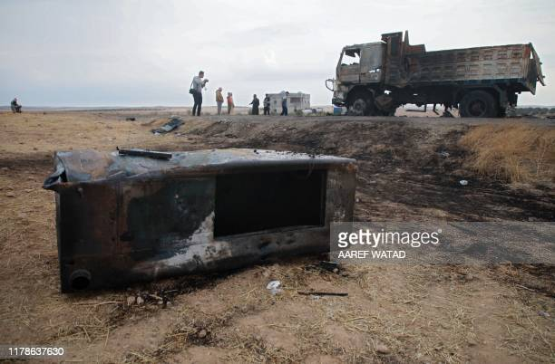 Picture taken on October 28 shows Syrian locals near a burnt metal container where a charred body was found and the destroyed truck which carried it,...