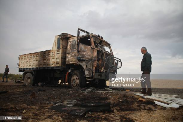 A picture taken on October 28 shows Syrian locals near a destroyed truck at the spot where Abu Hassan alMuhajir the Islamic State group's spokesman...