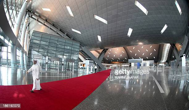 A picture taken on October 29 2013 shows a visitor walking on a red carpet at a terminal of Hamad International Airport in Doha AFP PHOTO / ALWATAN...