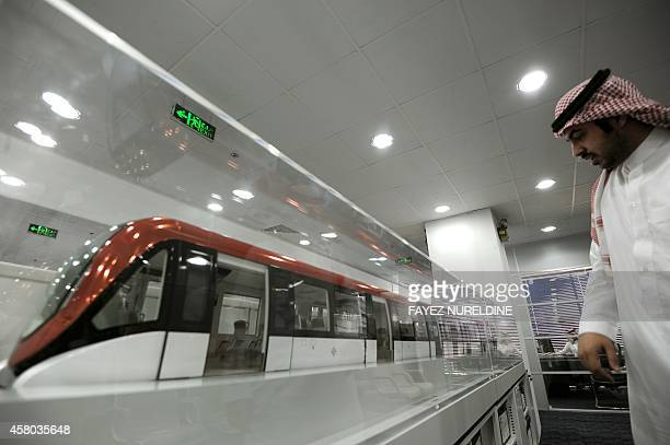 A picture taken on October 29 2014 shows Saudi Abdullah Allohaidan assistant of the director of the Riyadh Metro looking at a model of a train at the...