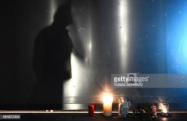 A picture taken on October 29 2015 shows a photo of the missing fouryearold asylumseeker Mohamed next to a candle at a make shift memorial site at...