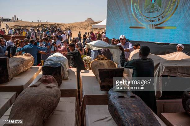 A picture taken on October 3 2020 shows Egyptian workers covering one of the sarcophaguses excavated by the Egyptian archaeological mission which...