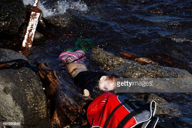 A picture taken on October 30 2015 shows the body of a child on the shore of the Greek island of Lesbos after boats transporting migrants and...