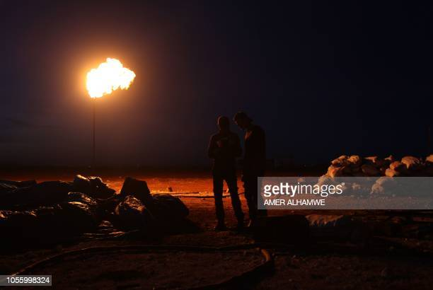 A picture taken on October 31 2018 shows two workers at a primitive oil facility in the town of Zardana in the countryside of the northwestern Syrian...