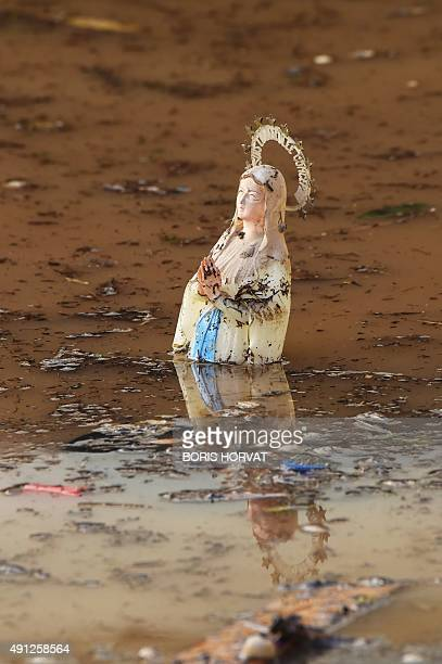 A picture taken on October 4 shows a statue of the Virgin Mary floating among waste in a flooded street in MandelieulaNapoule southeastern France...