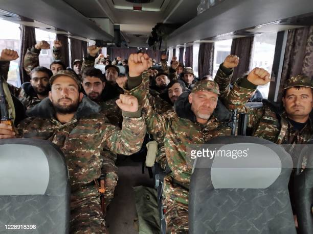 Picture taken on October 6, 2020 shows ehtnic Armenian volunteers and reservists riding in a bus on the Armenian territory towards the Karabakh...