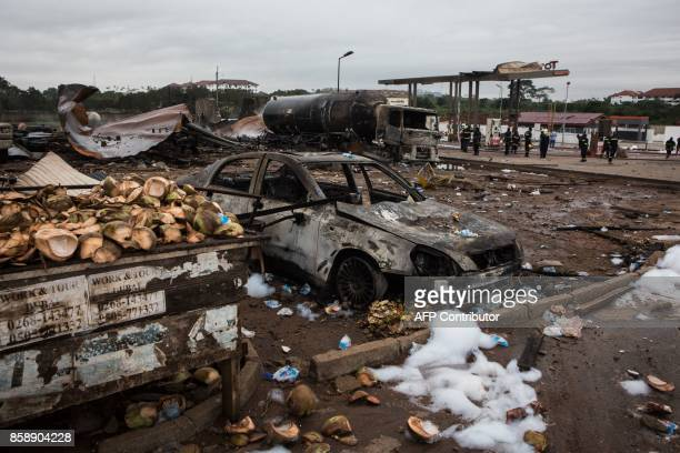 A picture taken on October 8 2017 in Accra shows burnt vehicles on the site where a gas tanker caught fire triggering explosions at two fuel stations...