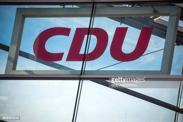 A picture taken on October 9 2017 shows a board with the logo of the German Christian Democratic Union party and a flag of the European Union...
