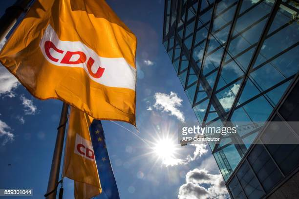 Picture taken on October 9, 2017 shows a flag with the logo of the German Christian Democratic Union party and a flag of the European Union...